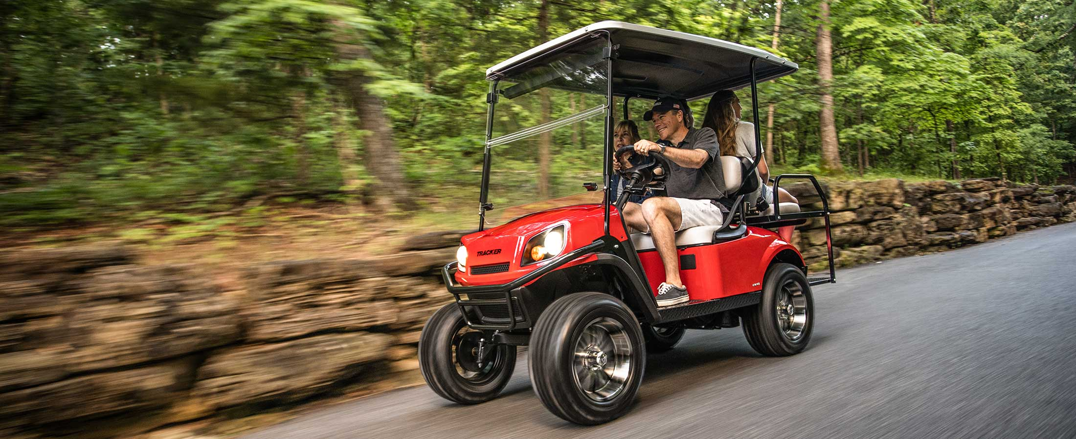 Family rides in a red LX4 personal Sport Cart beside a rock wall